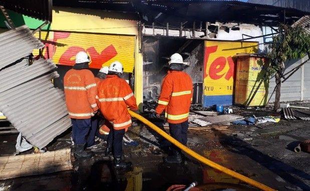 TERKENDALI: Petugas PMK melakukan pembasahan di lokasi kebakaran.
