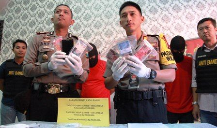 UANG PALSU: Petugas menunjukkan barang bukti dan tersangka kasus uang palsu yang diamankan di Mapolsek Genteng.