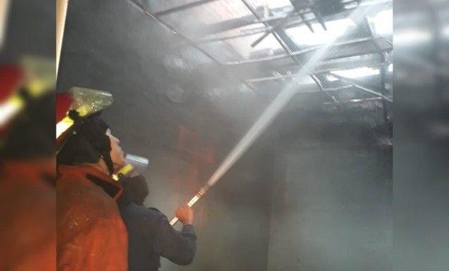 BERJIBAKU: Petugas pemadam kebakaran saat melakukan pembasahan di lokasi kejadian.