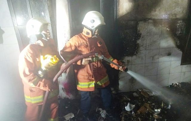 PEMBASAHAN: Petugas PMK memastikan tidak ada titik api di rumah milik Yulianti yang sempat mengalami kebakaran di lantai dua.