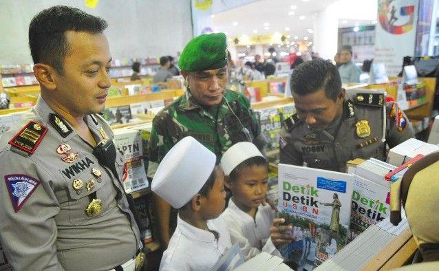 BELANJA: Kasatlantas AKP Wikha Ardilestanto dan anggota TNI dari Kodim 0817 mendampingi anak-anak yatim memilih buku yang akan dibelinya.