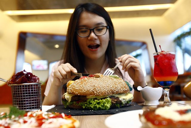 PAKAI PEWARNA ALAMI: Jessica Natalia siap menyantap Burger Thanos, menu burger terbaru Fairfield by Marriott Surabaya yang berukuran super besar.