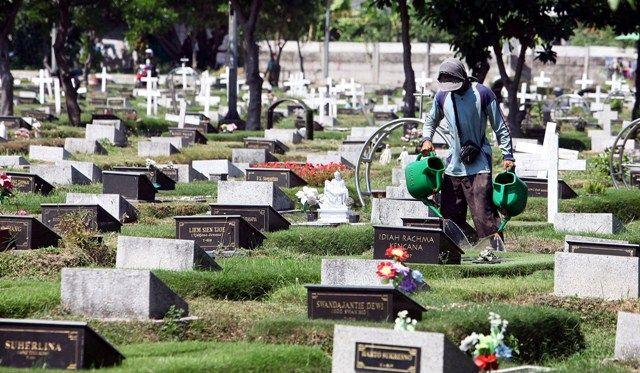 TERAWAT: Pekerja menyiram bunga di makam yang ada di lokasi Taman Pemakaman Umum (TPU) Keputih, Surabaya.
