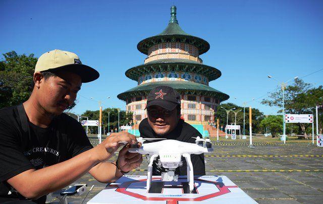 CARI ANGLE MENARIK: Dua orang peserta mempersiapkan drone miliknya dalam lomba drone racing di Ken Park.