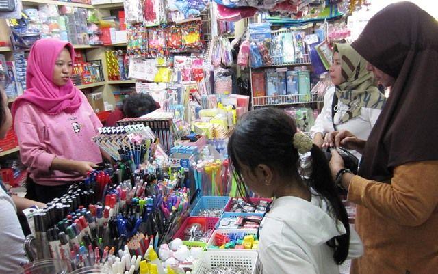 SELALU DICARI: Sejumlah orang tua melihat baju seragam sekolah dan alat tulis yang dijual di Pasar Blauran, Surabaya, Minggu (14/7).