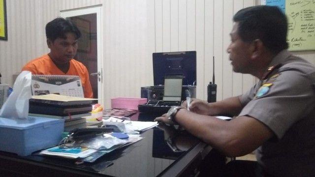 PAGAR MAKAN TANAMAN: Dwi Reza (kiri) yang diamankan karena mencuri uang di brankas kantornya sendiri.
