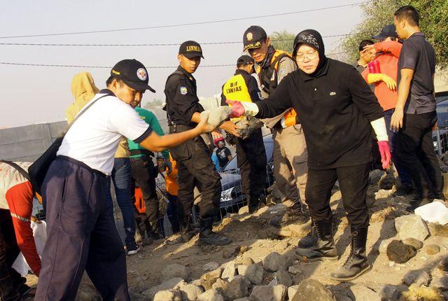 TURUN LANGSUNG: Wali Kota Surabaya Tri Rismaharini memimpin kerja bakti massal di sisi Jembatan Suramadu, Jumat (9/8).