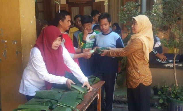 BERKURBAN: Wakil Kepala Sekolah Aisyiyah M.Datik  S.Pd M.Pd  membagikan daging kurban ke siswa dan warga.
