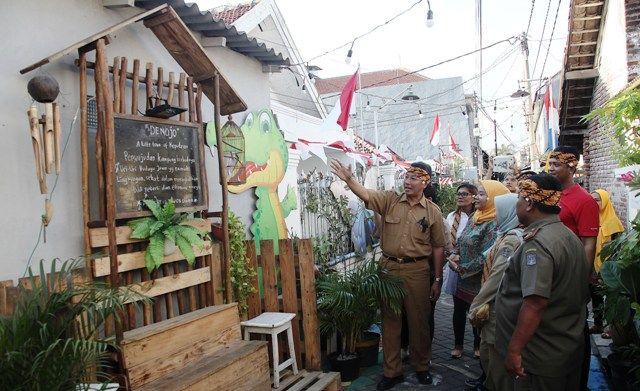 SPOT FOTO: Sekretaris DKRTH Surabaya Ipong Wisnoewardono (kiri) bersama kader lingkungan melihat sudut kampung Dinoyo Tengah, Surabaya, Senin (12/8).