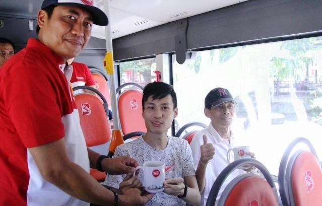 GRATIS: Kepala Dishub Surabaya Irvan Wahyudrajat memberikan suguhan minuman kepada penumpang saat uji coba rute baru Suroboyo Bus di Jalur MERR.