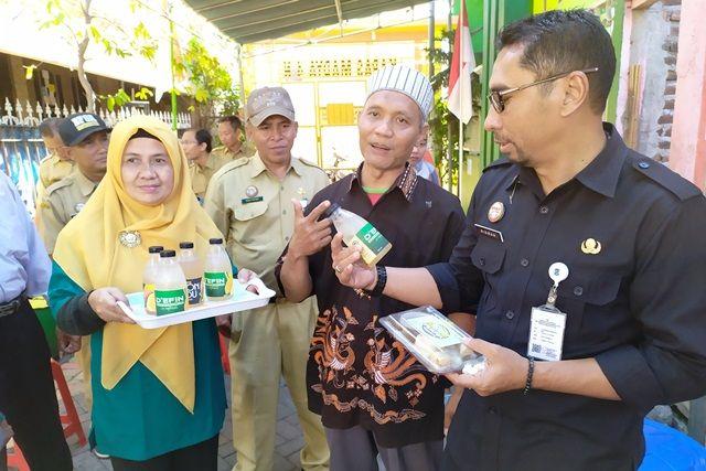 KELILING: Ketua RW 04 Kelurahan Pacar Keling (Jalan Karang Gayam) Sri Kartini (kiri) bersama sekretaris DKRTH Surabaya Ipong Wisnoewardono (kanan) saat sosialisasi SSC.