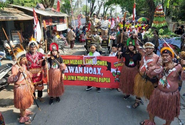 CINTA PAPUA: Warga RW 07 PPI Desa Suci menggunakan kostum khas suku Papua dan tentara BKR pada acara karnaval di Desa Suci, Kecamatan Manyar.