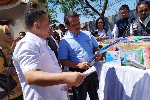 DOKUMEN TAK SESUAI: Ditjen PKTN Veri Anggrijono (kanan) menunjukkan beberapa barang impor illegal yang hendak dimusnahkan di pergudangan Jalan Tambak Langon, Surabaya.