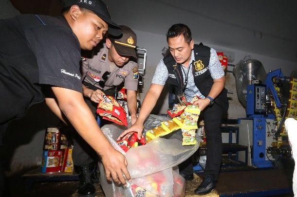 ILEGAL: Petugas menunjukkan barang bukti makanan ringan tanpa ijin yang diamankan di Jalan Zamhuri, Surabaya, Selasa (10/9).