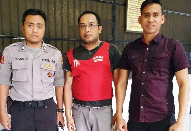 TERSANGKA: Yus Eriyanto (tengah) diamankan di Polrestabes Surabaya.