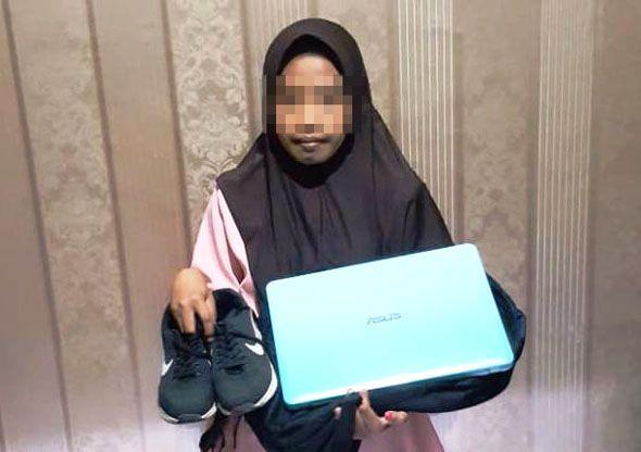 DIAMANKAN: Tersangka LEY menunjukkan barang bukti sepatu dan laptop yang diambil dari rumah majikannya.