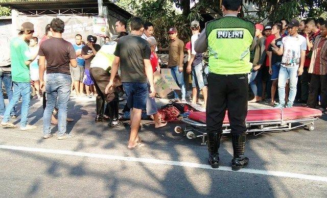 EVAKUASI: Petugas Laka Lantas Satlantas Polres Gresik dibantu warga mengevakuasi tubuh M. Muslih ke mobil jenazah.