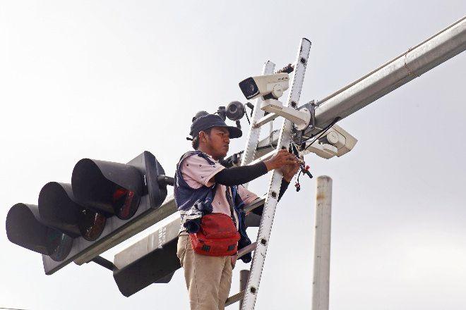 DITAMBAH: Pekerja menyelesaikan perbaikan rutin CCTV yang terpasang di traffic light Jalan Siwalankerto, Surabaya.