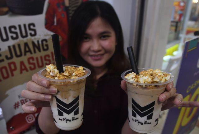 KOPI POP CORN: Seorang penikmat kopi menunjukkan sajian kopi yang dikombinasikan dengan pop corn, di salah satu gerai di ROyal Plaza Surabaya, Selasa
