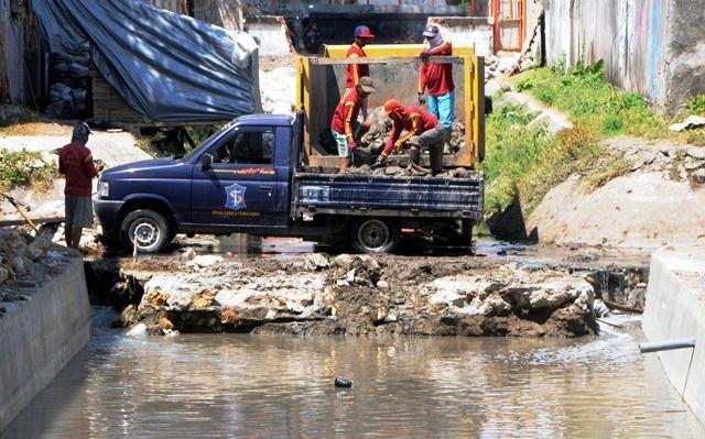 BERSIHKAN SALURAN AIR: Sejumlah petugas Satgas PU Bina Marga dan Pematusan Kota Surabaya melakukan pembersihan saluran air di kawasan Jalan Kartini.