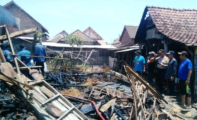 LUDES: Anggota PMK Kabupaten Gresik  dan warga melihat hasil rumah kosong yang terbakar api.
