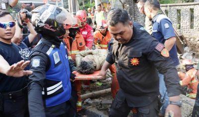 TERTIMBUN: Petugas gabungan mengevakuasi korban kecelakaan kerja di jalan Mayjen Sungkono, Surabaya, Rabu (23/10).