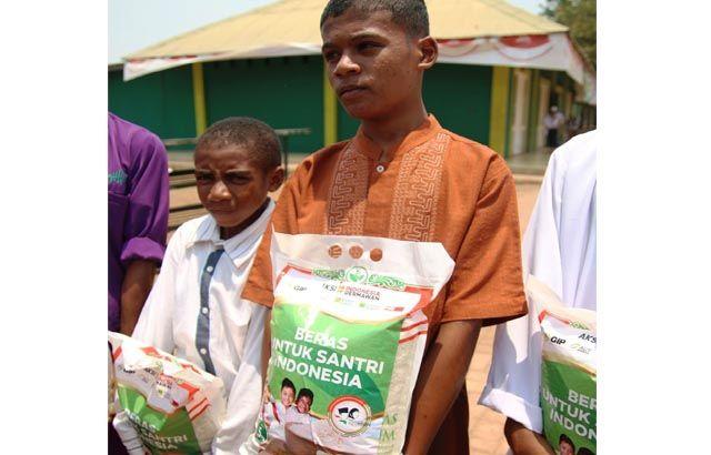 SUPPORT PANGAN: Para santri menenteng beras yang ia terima dari program BERISI.