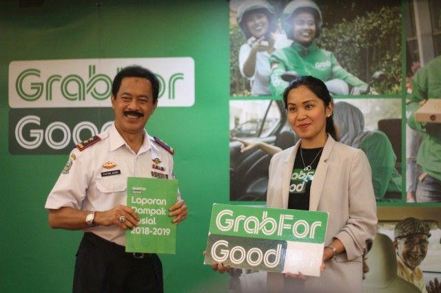 SINERGI: Kepala Dinas Perhubungan Provinsi Jawa Timur Fattah Jasin (kiri) didampingi oleh Deputy Head of Public Affairs Tirza Reinata Musunamy menunjukkan buku laporan dampak sosial Grab 2018-2019.