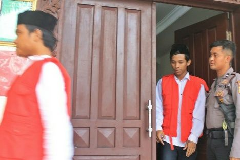 MENUNDUK: Kedua terdakwa Yuda Anjar Wicaksono dan Adi Tiyo Putro Yulianto usai menjalani persidangan di PN Gresik.