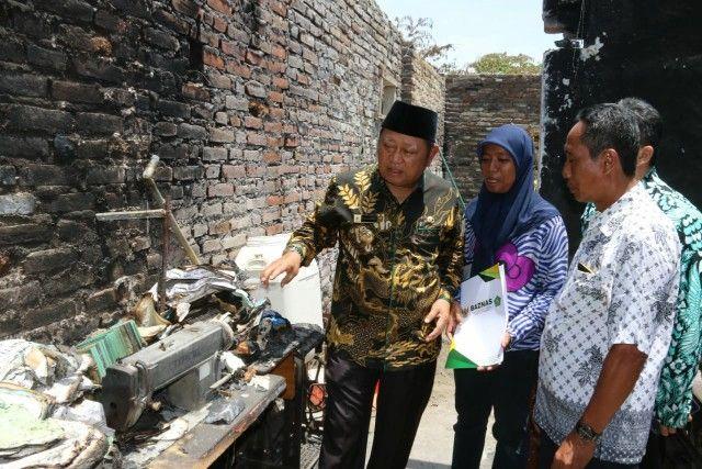 AKIBAT KORSLETING: Bupati Sidoarjo Saiful Ilah melihat kondisi rumah Siswandi yang hangus terbakar.