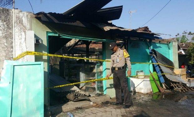 TERBAKAR : Polisi memasang garis police line di rumah yang terbakar milik Muntahari di Desa Gosari Kecamatan Ujungpangkah.