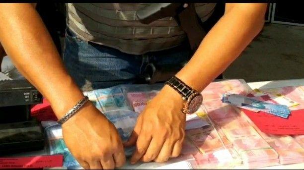 Petugas menunjukkan upal pecahan 100 ribu dan 50 ribu.