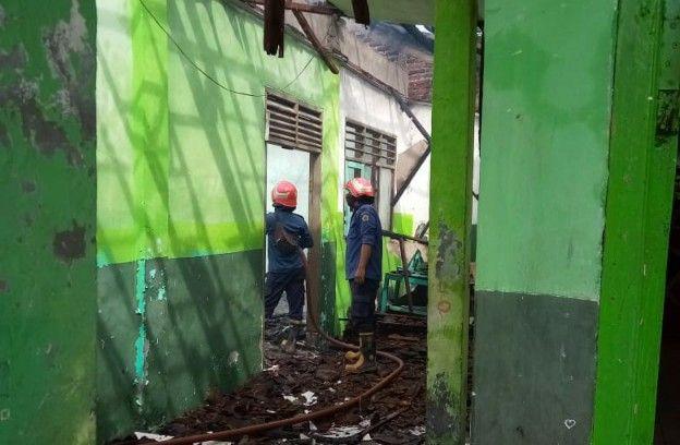 HANCUR: Anggota PMK Gresik melakukan pembasahan di ruang kelas SMP Nurul Huda di Jalan Kepatihan Menganti yang terbakar.