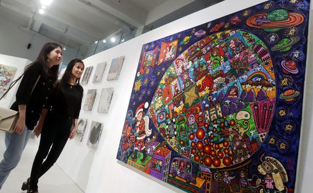 SENI LUKIS: Dua orang pengunjung Galeri Sumi Art Surabaya, mengamati salah satu karya lukis yang dipamerkan dalam ArtExhibition.