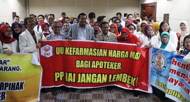 SEMANGAT: Ketua Umum PP Ikatan Apoteker Indonesia (IAI) Drs Nurul Eddy Pariang bersama anggota IAI Jatim, membentangkan spanduk dukungan UU Kefarmasia