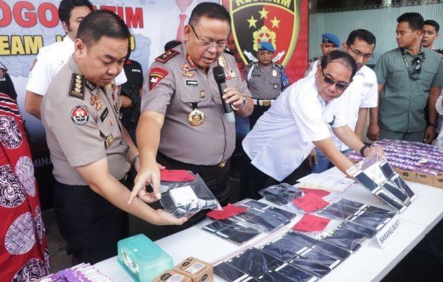 KENA BATUNYA: Kapolda Jatim Irjen Pol Luki Hermawan menunjukkan barang bukti dan tersangka kasus order fiktif ojek online yang diamankan di Mapolda Ja