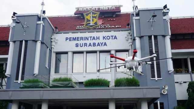 ANTISIPASI VIRUS: Drone yang mengangkut cairan disinfektan beraksi di Balai Kota Surabaya.