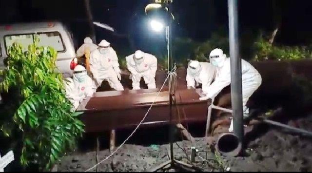 PAKAI PELINDUNG: Pemakaman jenazah pasien positif Covid-19 di TPU Delta Praloyo Kamis (26/3) dini hari.
