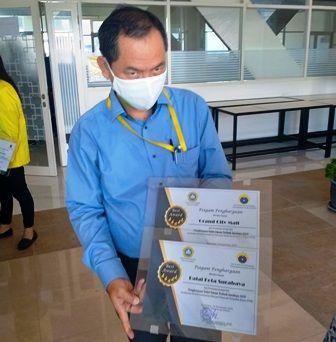 TERBAIK:  Lasman Parulian Purba memegang piagam penghargaan toilet umum terbaik di Surabaya.