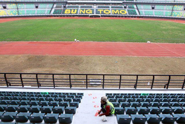 SIAP: Petugas memperbaiki tempat duduk di tribun Stadion GBT.