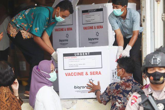 DISIMPAN: Pekerja menurunkan kardus berisi vaksin Sinovac untuk COVID-19 sesaat setelah tiba di gudang farmasi Dinas Kesehatan Pemkot Surabaya di Jalan Kalirungkut, Surabaya, Rabu (13/1).