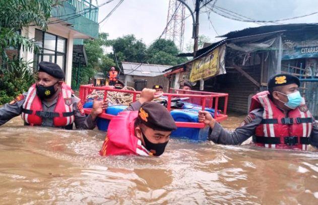 Anggota kepolisian dari Polda Metro Jaya membantu evakuasi korban banjir di Cipinang Melayu, Jakarta Timur.