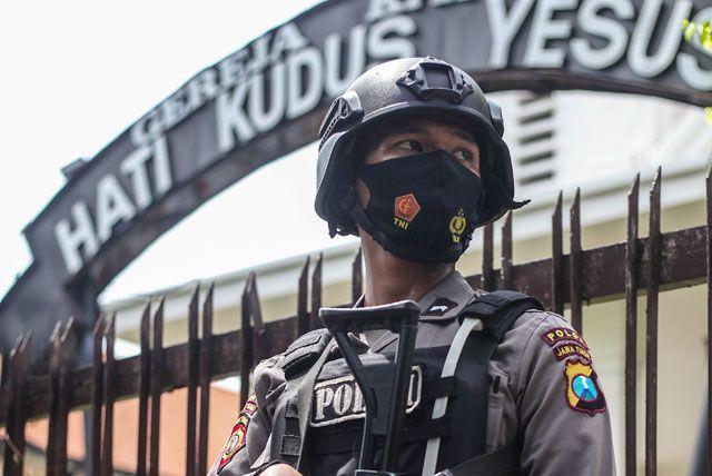 BERJAGA: Personel kepolisian dengan bersenjata lengkap bersiaga didepan gereja Hati Kudus Yesus, Jalan Polisi Istimewa, Surabaya, Jumat (2/4).
