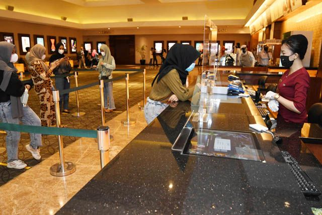 OPERASIONAL: Sejumlah penonton bersiap menonton bioskop yang mulai buka kembali di Grand City Mall, Surabaya, Jumat (2/4).