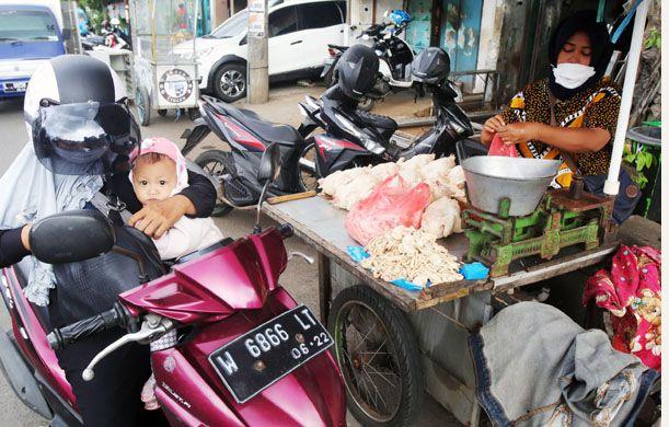 NAIK: Seorang ibu muda bersama bayinya berbelanja daging ayam di Pasar Tembok, Surabaya.