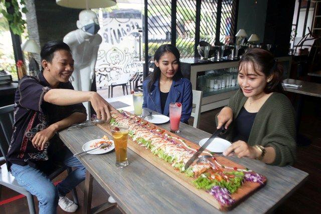 KUDAPAN TIMTENG: Sejumlah pelanggan menikmati sajian Kebab Limousine dengan panjang mencapai 1 meter yang cocok dinikmati ramai-ramai di salah satu hotel di pusat Kota Surabaya.