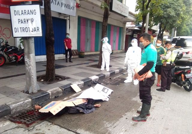 KORBAN LAKA: Petugas mengevakuasi jenazah korban di Jalan Mayjen Sungkono.