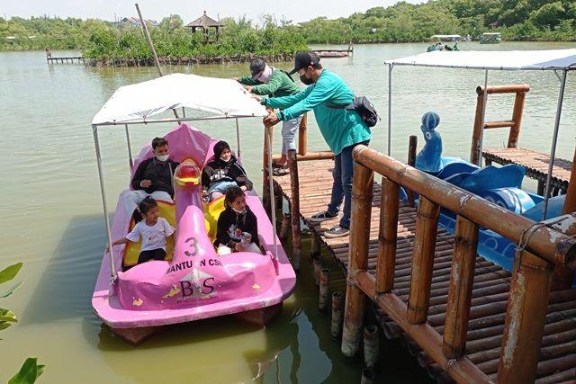 Warga menikmati suasana kawasan ekowisata Mangrove di Gunung Anyar Surabaya.