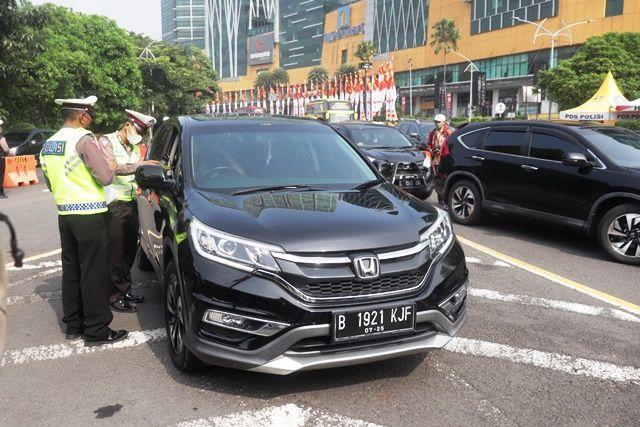 Petugas gabungan memeriksa kendaraan yang melintas di check point larangan mudik di bundaran Cito, Menanggal, Surabaya.