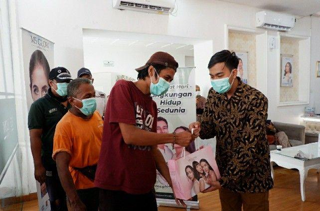 PEDULI: Usai diberi immune booster, Supervisor MS Glow Surabaya Agung Hari Laksono memberikan paket sembako ke petugas kebersihan.